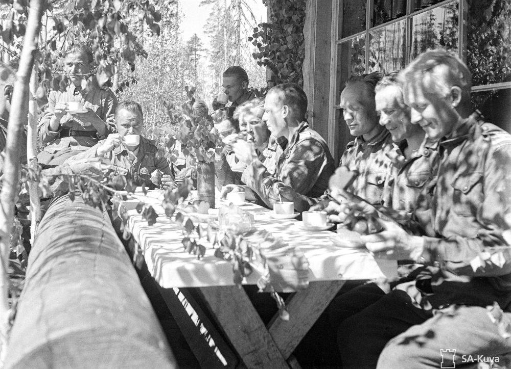 Erään etulinjan yksikön juhannuspäivä: Juhlan päälle saatiin korvikkeet. Orimattilan ja Mäntsälän poikia kahvilla. Mäntsäläläiset olivat yllättäneet koko yksikön lähettämällä pojille juhannukseksi oikeata vehnästä, jota riitti SUURI pala jokaiselle.